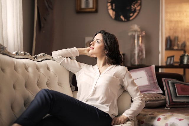 Tenant relaxing on a couch they personally bought. Landlords offering an unfurnished home.